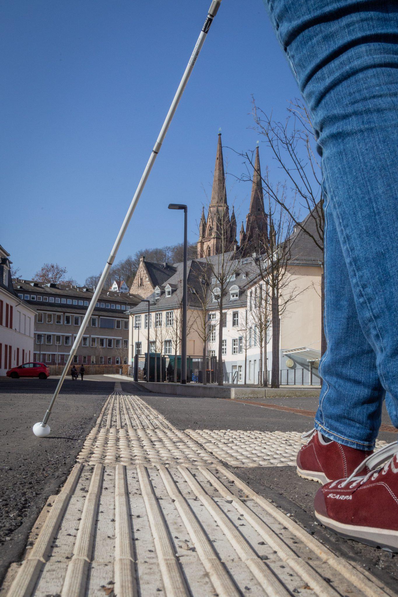 Nutzung eines Blindenleitsystems mit dem Langstock, Elisabethkirche Marburg im Hintergrund